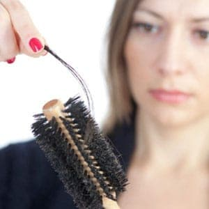 mother suffering postpartum hair loss pulling hair off a brush