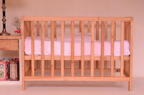 wooden crib with pink baby sheet