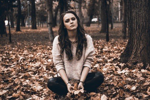 sad woman sat on ground full of leaves