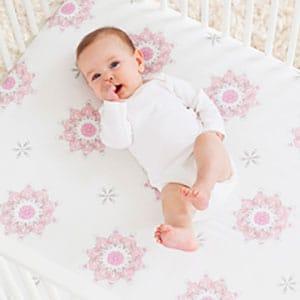 Baby laying on crib sheets