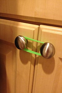 Baby proofing cabinets with a rubber band