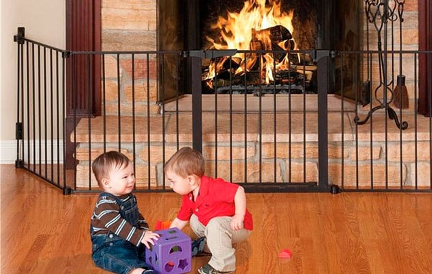 babys playing in front of a fire place baby proofed by a gate