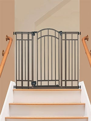Expandable baby gate sitting at the top of stairs