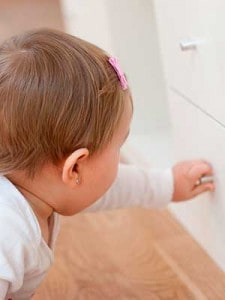 Baby opening a cabinet