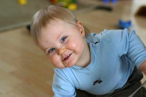 Baby in livingroom wearing blue jacket