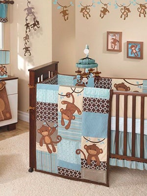 Blue and brown monkey themed baby nursery featuring comforter and mobile