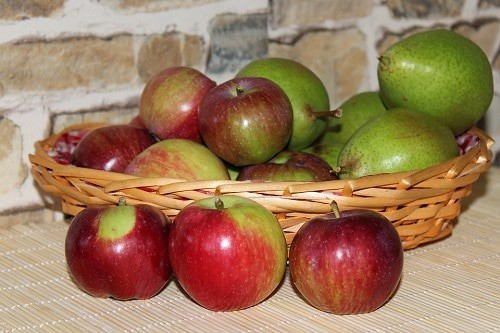 Apples and peaches in a brown basket