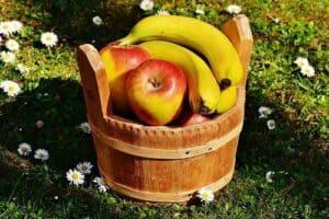 Banana and apple on th basket wood