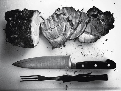 Grilled meat beside knife and fork