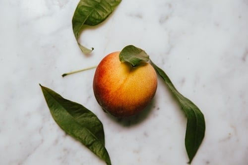 red peach with green leaves