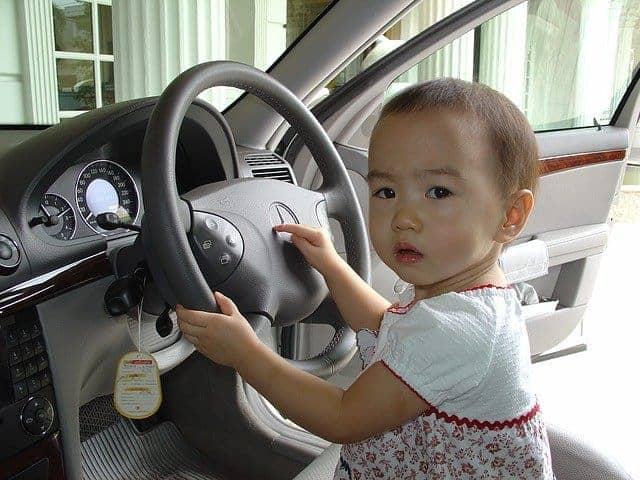 Baby inside a car wearing dress