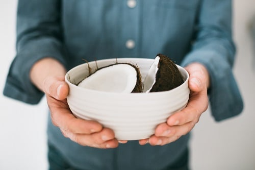 person holding white ceramic bowl with halved coconut