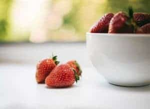 three red strawberries beside bowl with strawberries