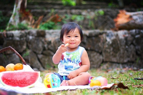 Baby sitting at the garden