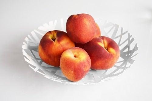 Round white plate of peaches