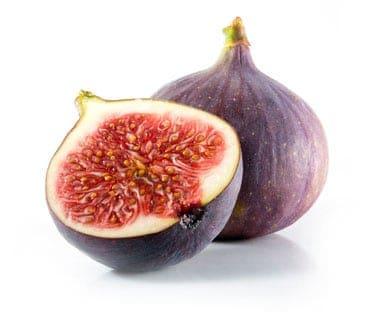 two figs, one cut in half revealing ripe red flesh