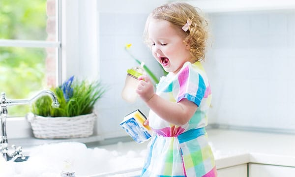 baby bottle being washed by small girl