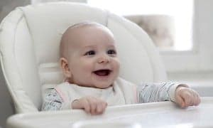 baby smiling while sitting in a high chair