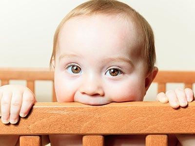 baby chewing on crib rail