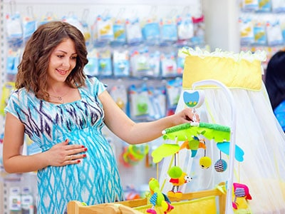 pregnant mother shopping for a brand new baby crib