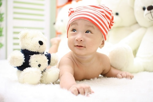 Smilling baby beside stuff toys