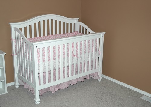 White crib with mattress inside