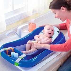 Mom cleaning baby in hammock baby bath tub