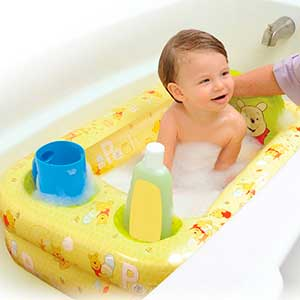 baby being washed in an inflatable baby bath tub