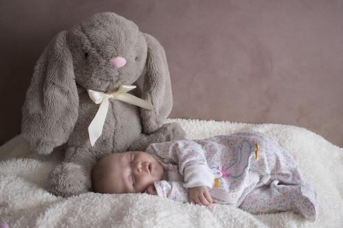 baby sleeping beside teddy bear