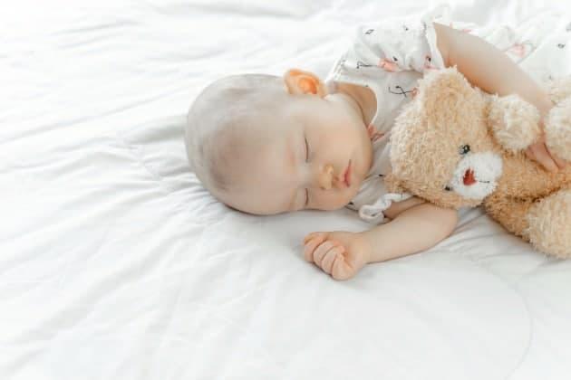 baby sleeping on mattress