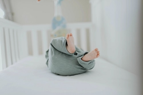 baby lying insede a crib wearing gray pants