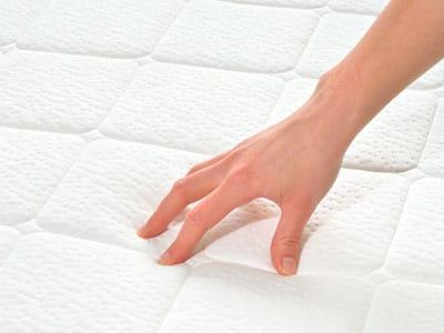 hand testing the firmness of a crib mattress