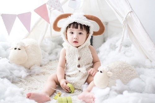 baby sitting beside white sheep plush toy