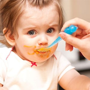 baby girl being spoon fed baby food with a blue spoon