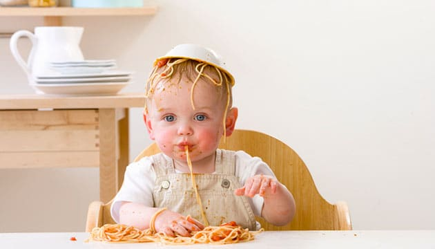 baby with spaghetti all over his face and clothes