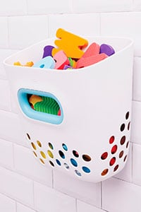 wall bucket toy storage colored white with bath toys piled inside