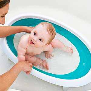 baby being washed in fold up bath tub