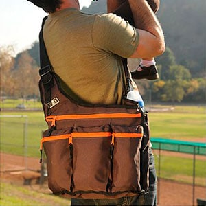 diaper bag being worn by dad carrying a baby