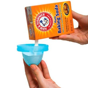 pouring baking soda into diaper pail container