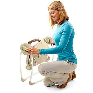 \portable baby swing being folded down into storage