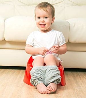 baby sitting on a potty chair with his pants down