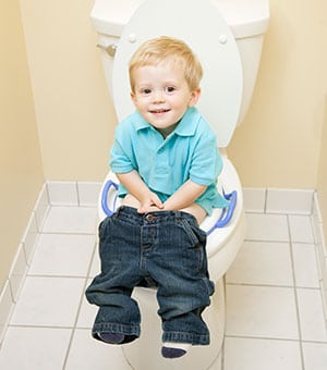 baby sitting on a potty seat with his pants down