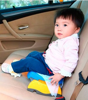 baby using travel potty in the back seat of the car