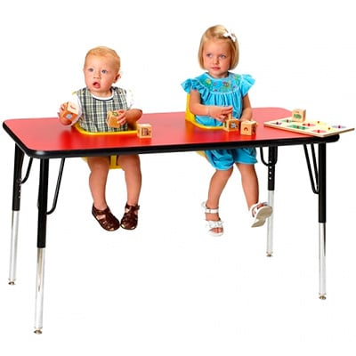 twins sitting at a high chair built into a table