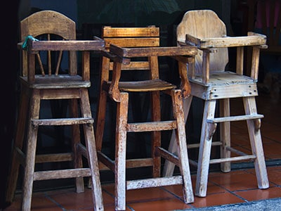 three old vintage wooden high chairs standing in a  row with peeling paint