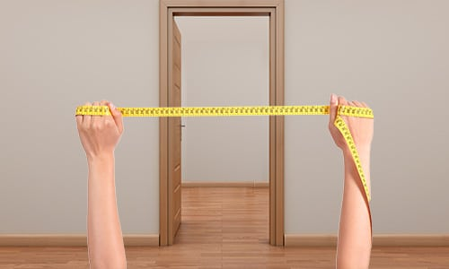 measuring up a doorway with a tape measure to fit a baby gate