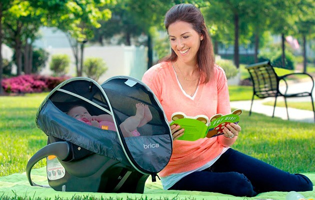 mom reading to her baby in one of the best baby car seat covers  by Brica