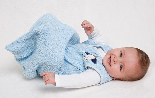 smiling baby wearing a sleep sack