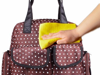 wiping down a dirty diaper bag with a cloth
