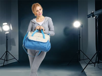 woman holding a diaper bag in a photography studio